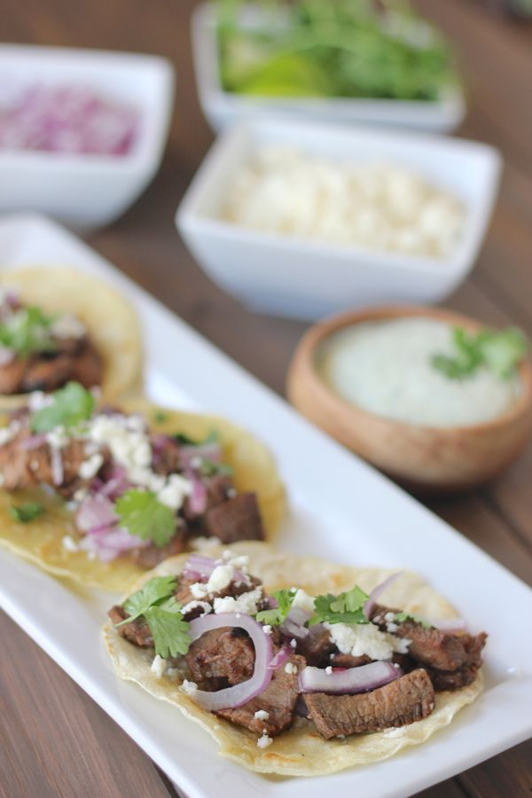 Steak Tacos With Cilantro Lime Cream - tender grilled steak tacos, red onions, queso fresco and cilantro lime cream on a lightly fried white corn tortilla