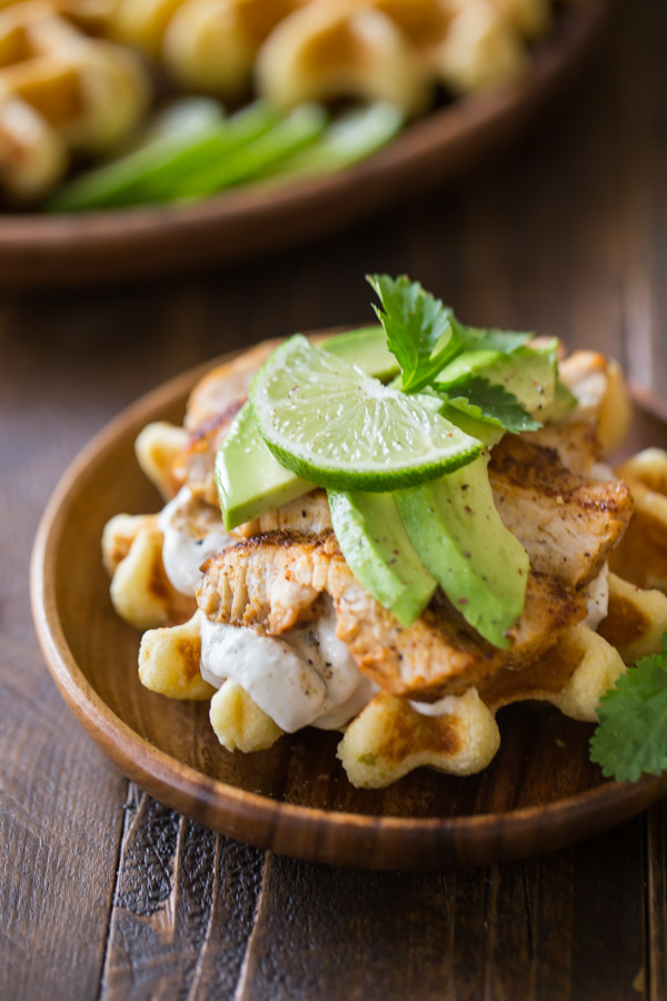 Green Chile Chicken Waffletada - A mini cornbread waffle served tostada style, topped with a green chile cream, grilled chicken, and avocado!