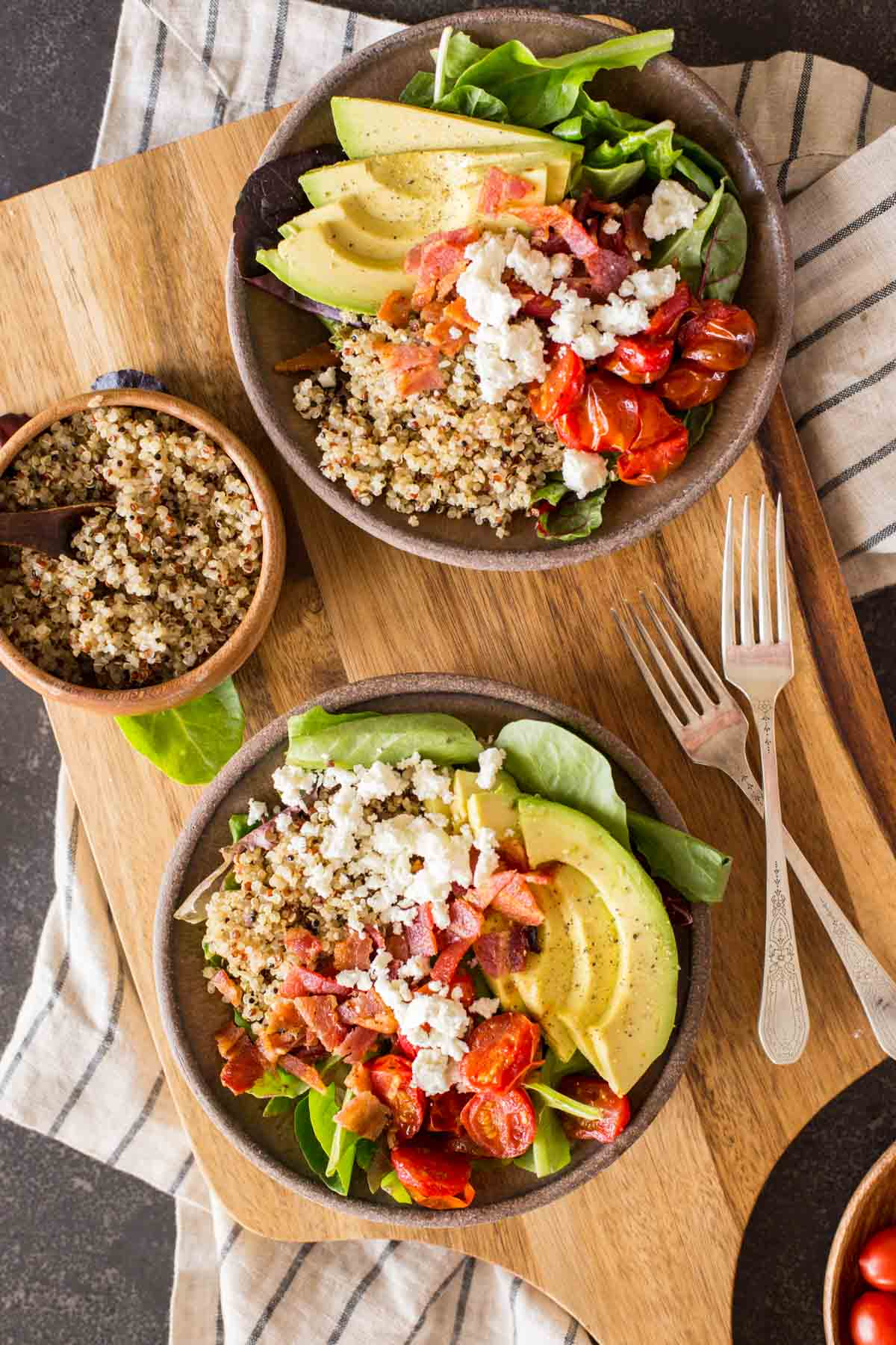 These BLT Bliss Bowls have so much going on! They've got mixed baby greens, oven roasted tomatoes, crisp bacon, avocado, nutty quinoa, and creamy feta.